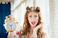 Schöne glückliche lächelnde Pinupfrau, die Wecker zeigt Stockfotos