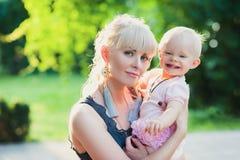 Schöne glückliche Mutter, die draußen Baby mit Sommerhintergrund der Liebe umarmt Stockbilder