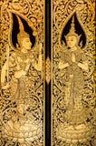 Schöne goldene thailändische Malerei auf der Tür im tample Stockfotos
