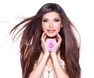 Schöne hübsche Frau mit langer Haar- und Rosarose am Gesicht. Stockfoto