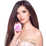Schöne hübsche Frau mit langer Haar- und Rosarose am Gesicht Lizenzfreie Stockfotos
