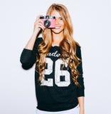 Schöne Hippie-Frau, die Fotos mit rosa Retro- Filmkamera auf weißem Hintergrund macht Schönes Brunette-Mädchen mit Frisur und bil Lizenzfreies Stockfoto