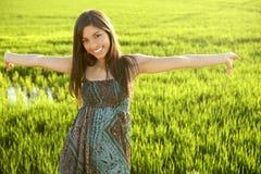 Schöne indische Frau auf den grünen Reisgebieten Stockfotografie