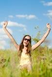 Schöne Jugendliche, die Spaß hat. glückliche lächelnde u. schauende junge Frau der Kamera auf Hintergrund des Sommergrüns draußen Stockbild