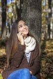 Schöne Jugendliche, die am Telefon sitzt und spricht Lizenzfreie Stockfotos