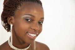 Schöne junge afrikanische Frau, die ein Glas Rotwein hält Stockfotografie