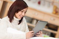 Schöne junge Asiatin, die mit einer Tablette sich entspannt Lizenzfreie Stockfotos