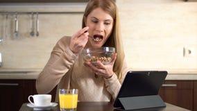 Schöne junge attraktive Frau, die Corn-Flakes zum Frühstück isst und ihre Tablette verwendet Tasse Kaffee stock video