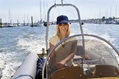 Schöne junge blonde Frau, die ein Schnellboot antreibt Stockbild