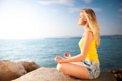 Schöne junge blonde Frau, die herein auf einem Strand bei Sonnenaufgang meditiert Lizenzfreie Stockbilder