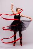 Schöne junge Blondineballettturnertraining calilisthenics Übung mit rotem Band mit roten Schuhen Stockbild