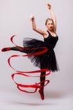 Schöne junge Blondineballettturnertraining calilisthenics Übung mit rotem Band mit roten Schuhen Lizenzfreies Stockbild