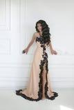 Schöne junge Brunettefrau im eleganten Kleid mit langem gewelltem h Lizenzfreie Stockfotos