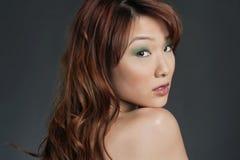 Schöne junge Chinesin, die zurück über farbigem Hintergrund schaut Stockfotografie