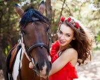 Schöne junge Dame, die das rote Kleid reitet ein Pferd am sonnigen Sommertag trägt Brunette mit dem langen gelockten Haar mit Blu Lizenzfreies Stockfoto