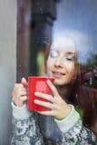 Schöne junge Frau auf einem Balkon hinter dem Glas Stockbild