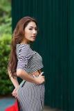 Schöne junge Frau, die allein am Café im Freien aufwirft Lizenzfreie Stockfotografie