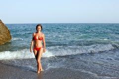 Schöne junge Frau, die auf dem Strand aufwirft Stockfotos