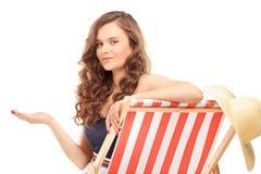 Schöne junge Frau, die auf einem Sonnenruhesessel sitzt und Esprit gestikuliert Stockbilder