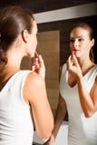 Schöne junge Frau, die auf Make-up in das Badezimmer sich setzt Stockfotografie