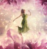 Schöne junge Frau, die auf riesige Blume springt Stockfotos