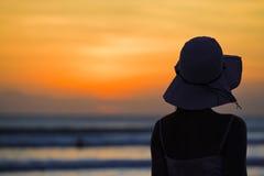Schöne junge Frau, die auf Strand steht Stockfoto