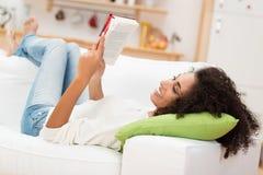 Schöne junge Frau, die ein Buch liest Lizenzfreie Stockbilder