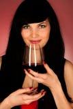 Schöne junge Frau, die ein Glas Rotwein hält Stockfotos