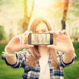 Schöne junge Frau, die ein selfie Foto mit Telefon macht Stockbild