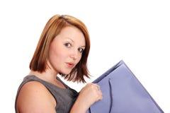 Schöne junge Frau, die in eine Einkaufstasche späht Lizenzfreie Stockbilder