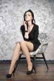 Schöne junge Frau, die in einem Lehnsessel sitzt Schwarzes Kleid, Schuhe und Strümpfe Lizenzfreies Stockbild
