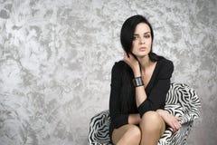 Schöne junge Frau, die in einem Lehnsessel sitzt Schwarzes Kleid, Schuhe und Strümpfe Stockfotos