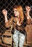 Schöne junge Frau, die hinter metallischem Gitter steht Stockbild