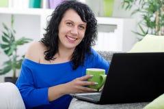 Schöne junge Frau, die an ihrem trinkenden Hauptcoffe, lächelnd sitzt Stockfotos