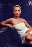 Schöne junge Frau, die im Badtuch sitzt Stockbild