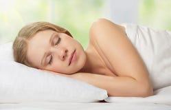 Schöne junge Frau, die im Bett schläft Stockfotografie