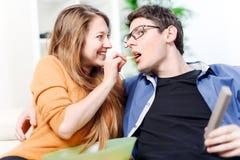 Schöne junge Frau, die Lebensmittel zu ihrer Lieblingsfront des Fernsehens gibt Stockfotos