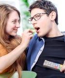 Schöne junge Frau, die Lebensmittel zu ihrer Lieblingsfront des Fernsehens gibt Lizenzfreie Stockfotografie