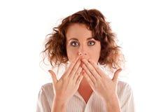 Schöne junge Frau, die mit ihren Händen über ihrem Mund keucht Stockfoto