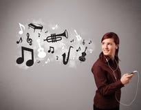 Schöne junge Frau, die Musik mit musica singt und hört Stockbild
