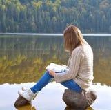 Schöne junge Frau, die nahe einem See sich entspannt Stockbild