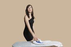 Schöne junge Frau, die oben beim Bügeln des Hemdes über farbigem Hintergrund schaut Stockbild