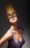 schöne junge Frau, die schwarze Karnevalsschablone trägt Lizenzfreies Stockbild