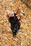 Schöne junge Frau, die Spaß im Herbstpark hat Stockbild