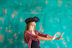 Schöne junge Frau, die Spiel in den Gläsern der virtuellen Realität spielt Stockbild