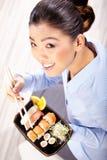 Schöne junge Frau, die Sushi isst Flache Schärfentiefe, Fokus ist auf den Augen Stockbilder