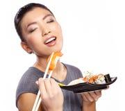 Schöne junge Frau, die Sushi isst Flache Schärfentiefe, Fokus ist auf den Augen Stockfotos