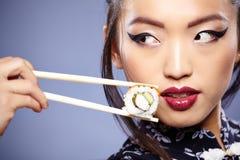 Schöne junge Frau, die Sushi isst Flache Schärfentiefe, Fokus ist auf den Augen Lizenzfreies Stockfoto