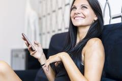 Schöne junge Frau, die Telefon verwendet Lizenzfreies Stockfoto
