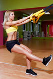 Schöne junge Frau, die TRX-Übungen tut Stockbilder
